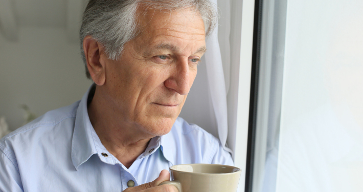 Senior man looking by window, holding cup of tea